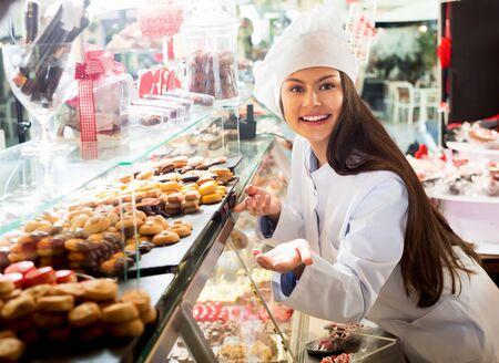 Jeune fille souriante au chapeau vendant des chocolats fins et des pâtisseries sucrées