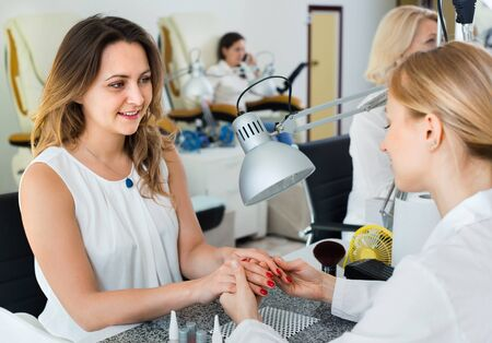 Two charming   women clients having manicure done in nail salon