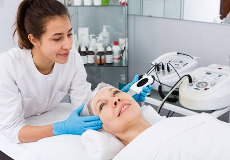 Aged woman making beauty procedures for face in spa salon Stockfoto