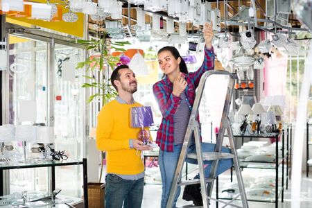 Woman and man in shop of home appliances are choosing stylish and modern chandelier lamp.