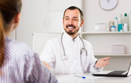 Positive man doctor with female client in hospital