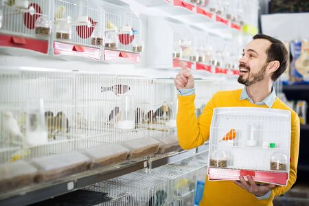 happy male customer deciding on best bird to keep in pet shop Stockfoto