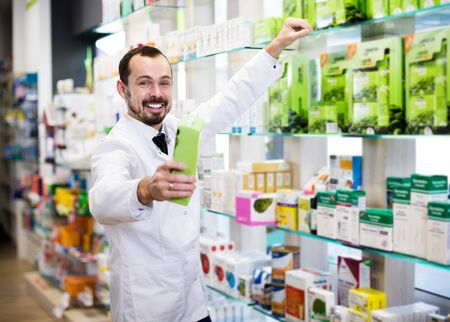 Smiling male pharmacist offering reliable drugs in drugstore