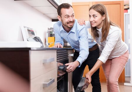 Young loving couple choosing household appliances for their kitchen in store