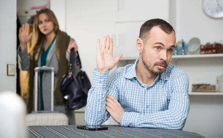 Annoyed man sitting at table and gesturing enough while his girlfriend leaving him