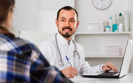 Female visitor consulting satisfied pleasant  man doctor in hospital Stockfoto