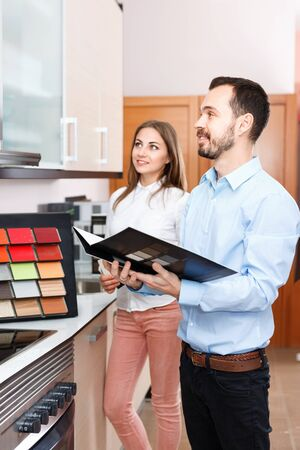 Competent smiling positive seller consulting female customer in store of kitchen furnishing and appliances Stock Photo