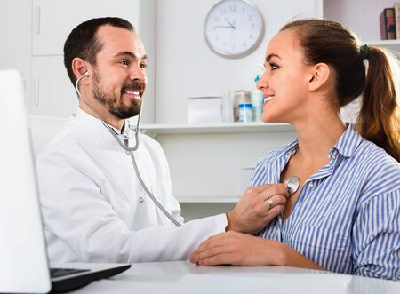 Female visitor consulting  friendly  man doctor in hospital