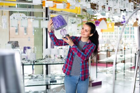 European girl in lighter shop is choosing stylish and modern lamp for house interior.