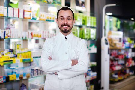 Smiling  positive male pharmacist demonstrating assortment of drugs in pharmacy Imagens