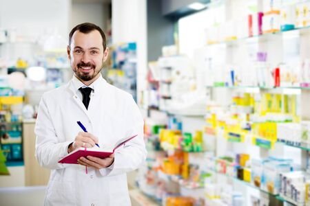 Young male pharmacist checking assortment of drugs in pharmacy Stockfoto