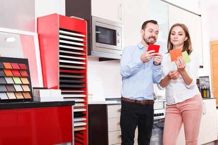 Happy couple choosing stylish materials for kitchen furnishing in store Stok Fotoğraf