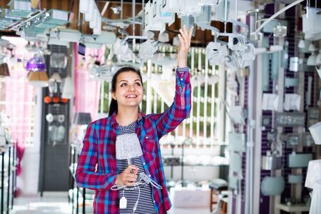 Smiling happy  girl in lighter shop chooses stylish and modern chandelier lamp 스톡 콘텐츠