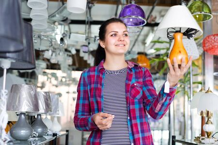 Woman in lighter shop is choosing stylish and modern lamp for house interior.