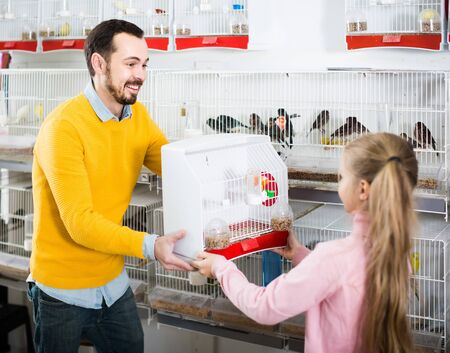 happy american man seller demonstrating canary bird in cage to girl in pet shop