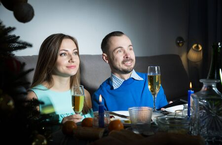 Portrait of couple in festive mood during celebration of Christmas watching tv in dark room