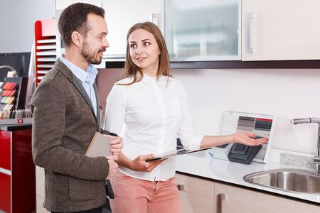 Glad couple choosing new kitchen mixer tap in furnishing store