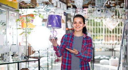 Girl 18-20 years old in lighter shop is choosing stylish and modern lamp for house interior.