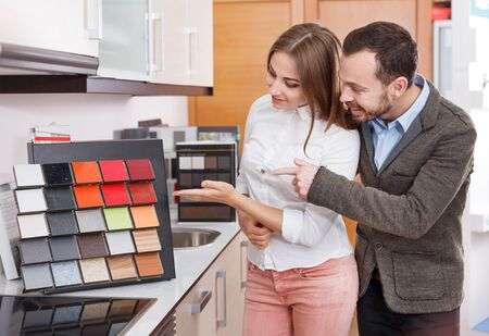 Loving couple choosing a kitchen furniture materials for their apartment. Focus on woman