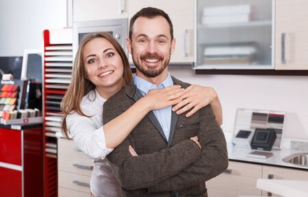 Loving couple choosing new kitchen furniture in store, enjoying time together