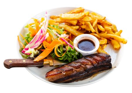 French cuisine, duck breast Magret with raspberry sauce served with vegetable salad and french fries. Isolated over white background