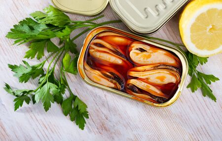 Appetizing pickled mussels in oil in open tin can on wooden table with fresh parsley, lemon and spices