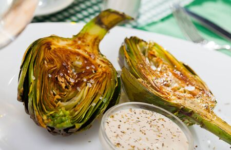 Delicious roasted  halves of artichokes served with coarse salt  on plate Stock fotó