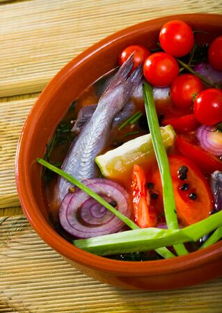 Fisherman soup - broth of blue whiting fish with tomatoes, lemon and bell peppers served in bowl