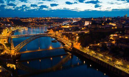 Panoramablick auf das beleuchtete Stadtbild von Porto und Ponte Dom Luis I über den Fluss Douro bei Nacht, Portugal