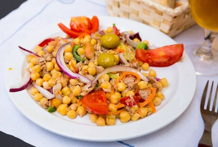 Empedrado garbanzos, traditional spanish salad with chickpeas, crumbled cod, olives, tomato, onion and bell pepper