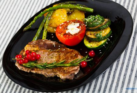 Veal with baked vegetables is tasty dish in the kitchen.