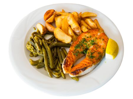 Healthy dinner, grilled salmon fillet with roasted potatoes, stewed green beans and lemon. Isolated over white background Stockfoto - 130036305