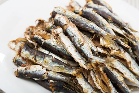 Image of dish of  many tasty baked anchovy served on plate at table Stok Fotoğraf - 130036306