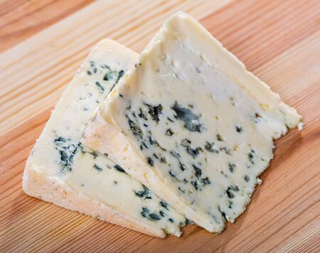Slices of piquant soft blue cheese on wooden surface Stok Fotoğraf