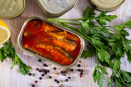 Picture of  tasty sardines in tomato sauce on background with greens and lemon Stock Photo