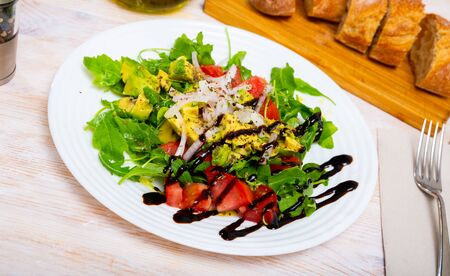 Appetizing vegetarian salad with fresh tomatoes, avocado, onion and arugula Stock fotó