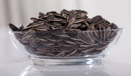 Unshelled sunflower seeds in oval glass bowl on white surface. Organic snack Stock fotó