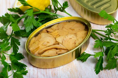 Appetizing tunny in oil in open tin can on wooden table with fresh parsley and lemon