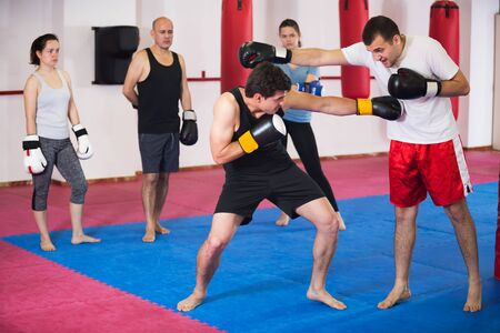Two athlete men in sportswear exercising boxing sparring at box class 免版税图像