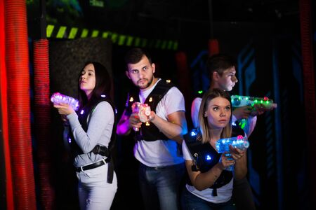 Modern young people with laser pistols playing laser tag on dark labyrinth