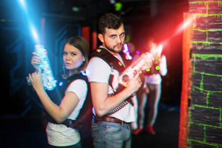 Young man and woman standing back to back with laser pistols in lasertag room on bright beams