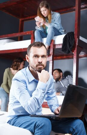 Upset bearded man sitting with laptop on bed in modern hostel bedroom