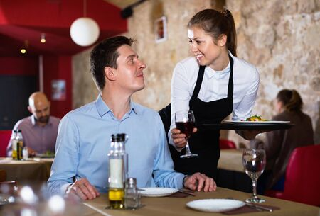 Diligent friendly polite waitress serving ordered dishes to smiling man at restaurant