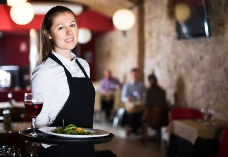 Portrait of polite waitress wearing apron holding tray with dishes in restaurant interior Archivio Fotografico