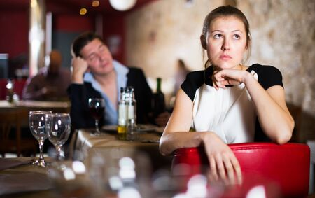 Offended young woman on background with drunk man at restaurant table Reklamní fotografie