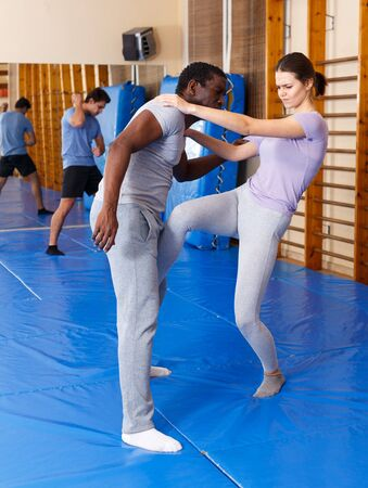 Adult people practicing effective techniques of self-defence in sports club