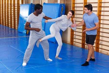 Young girl working in pair with African American man mastering new self defence moves with male coach