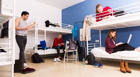 Young positive travelers communicating while resting in hostel sleep room