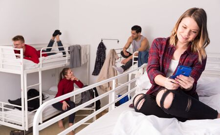 Happy young woman traveler resting with phone on two-story bed in hostel dorm