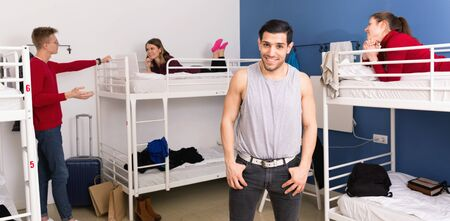 Glad pleasant smiling handsome Hispanic man smiling while standing in bedroom of hostel Stock Photo
